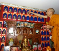Our event\'s presiding monk, Lama Youngdrung places each empowered Buddha statues in place marked by the pledger\'s name plaque.